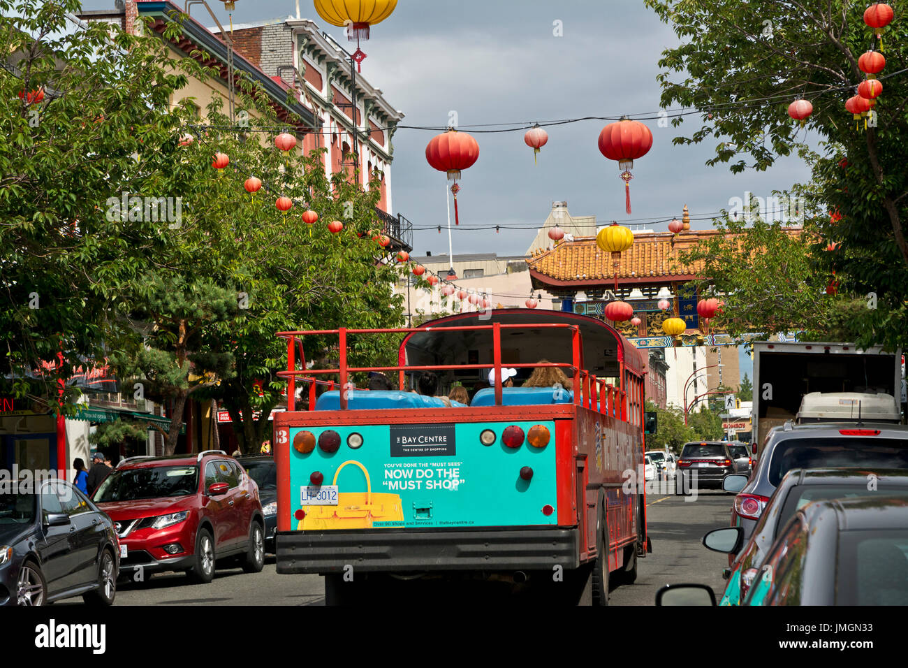 Bus tour with tourists on the streets of Chinatown in Victoria, British Columbia, Canada - Stock Image