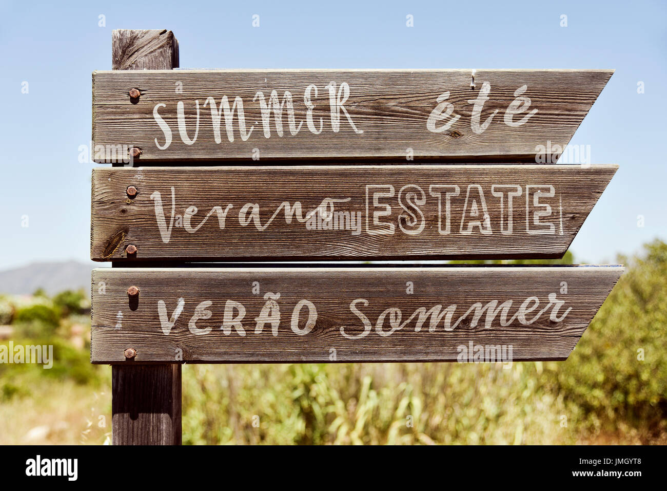 closeup of a rustic wooden signpost in a natural landscape with the word summer written in english, french, spanish, Stock Photo