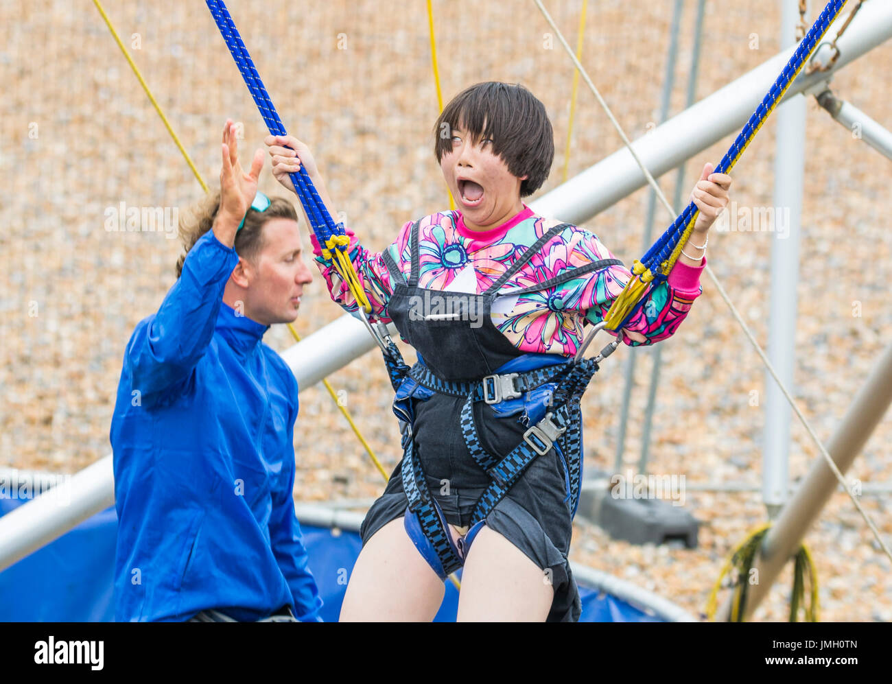 Young Japanese girl making a funny excited face as she enjoys herself on a Bungee Jump Trampoline. Bungee Jump Trampoline. - Stock Image