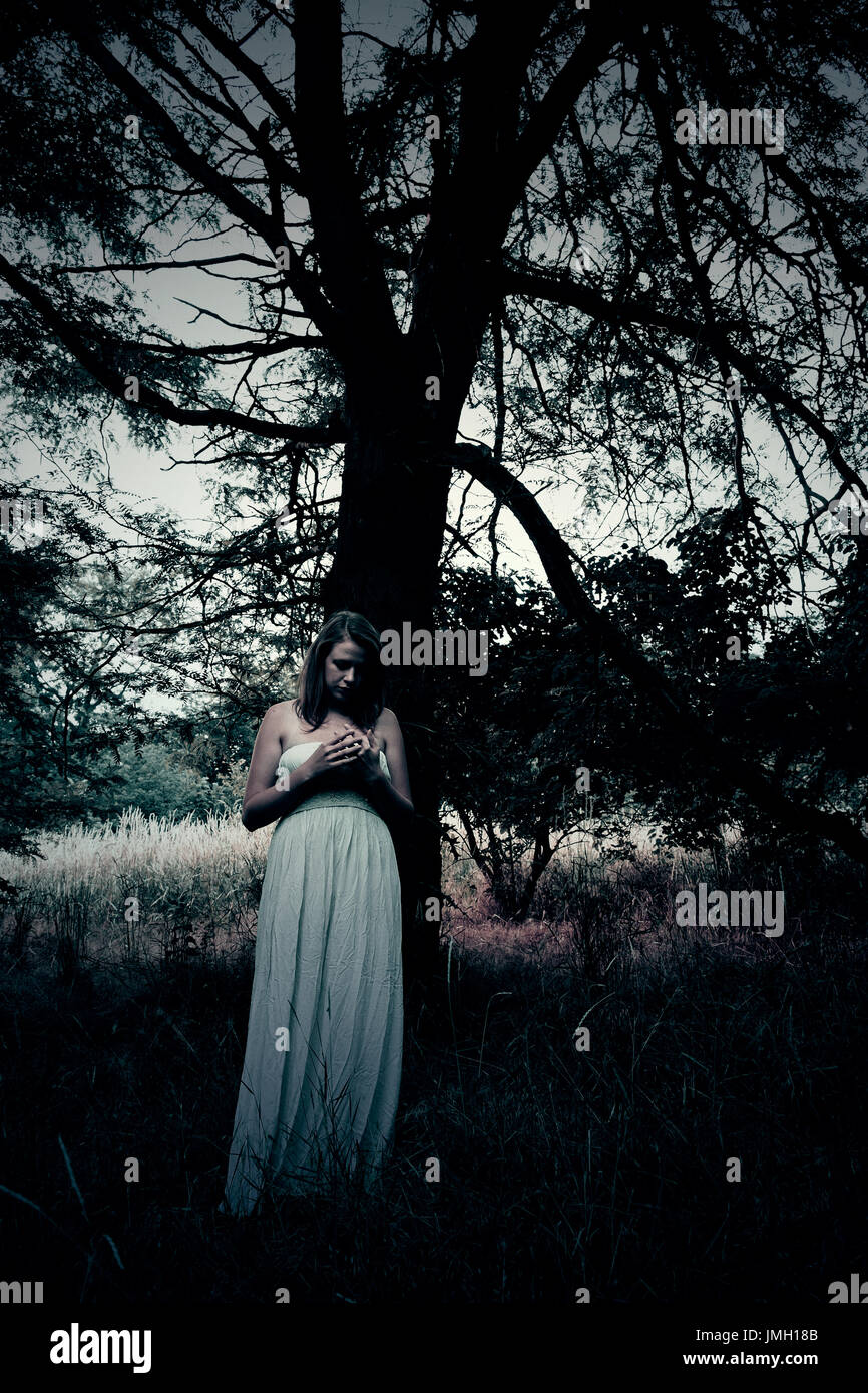 Spooky dangerous woman in night forest. Ideal for book cover - Stock Image