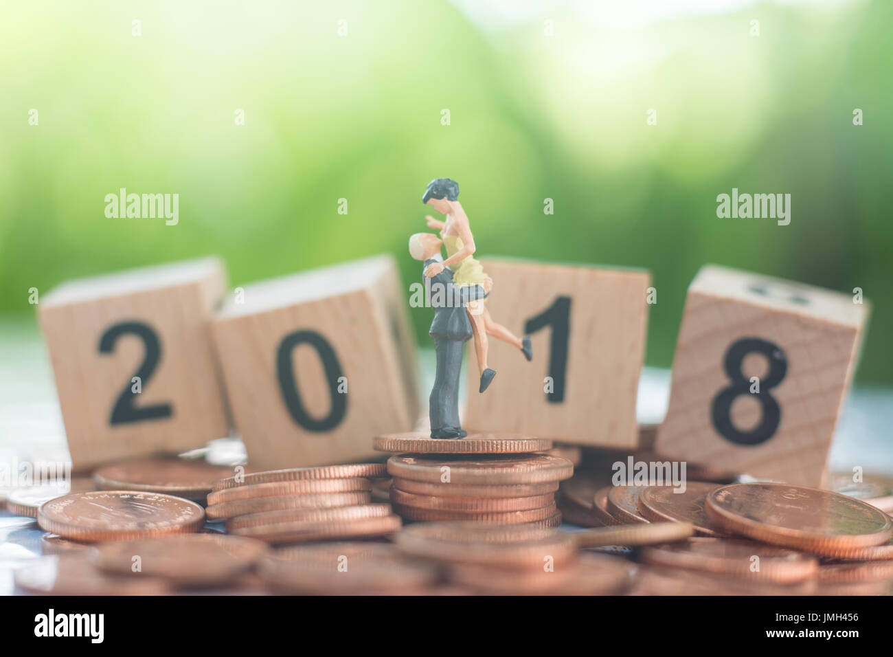 The man pick the woman up with love and happiness on the pile of coins and wooden number 2018 background using as growing together, teamwork. - Stock Image