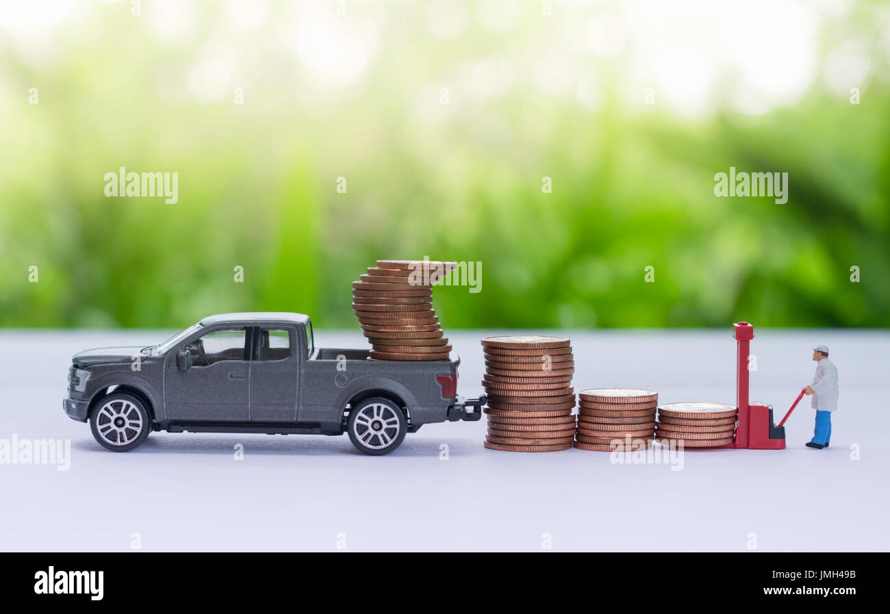Miniature truck carrying stack of coins, worker loading stack of coins using as a business concept. - Stock Image