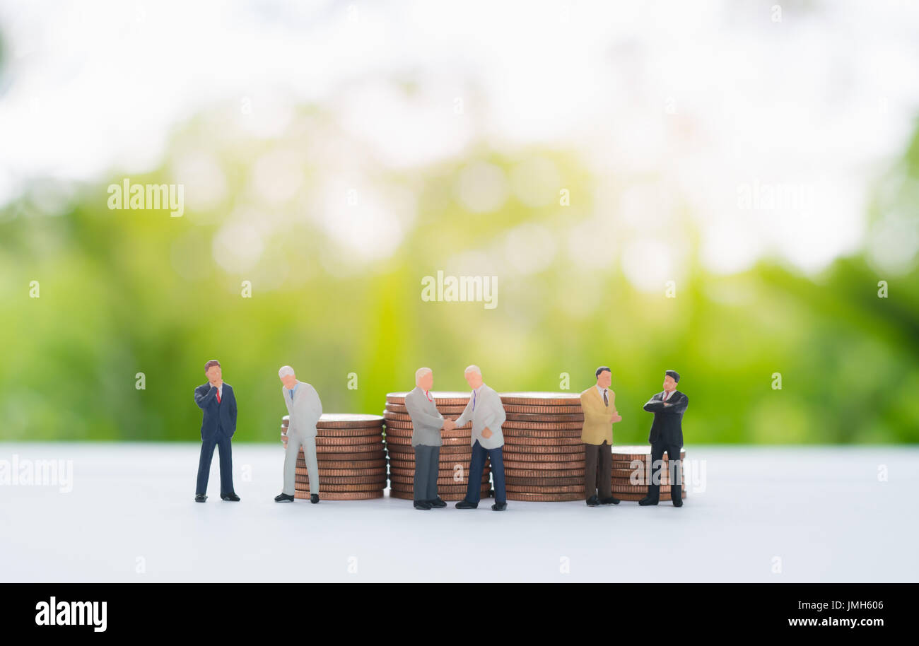 Stack of coins behind miniature businessman handshaking, discussing, negotiating using as background commitment, agreement, investment and partnership - Stock Image
