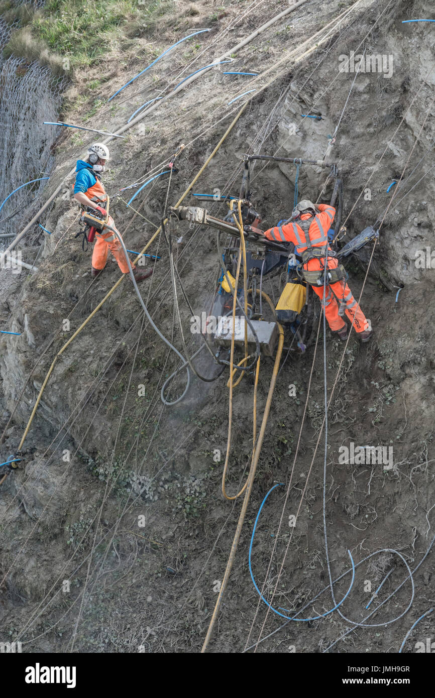 Telephoto shot of two workmen drilling holes for cliff stabilisation rock bolts and subsequent rockfall mesh attachment. - Stock Image