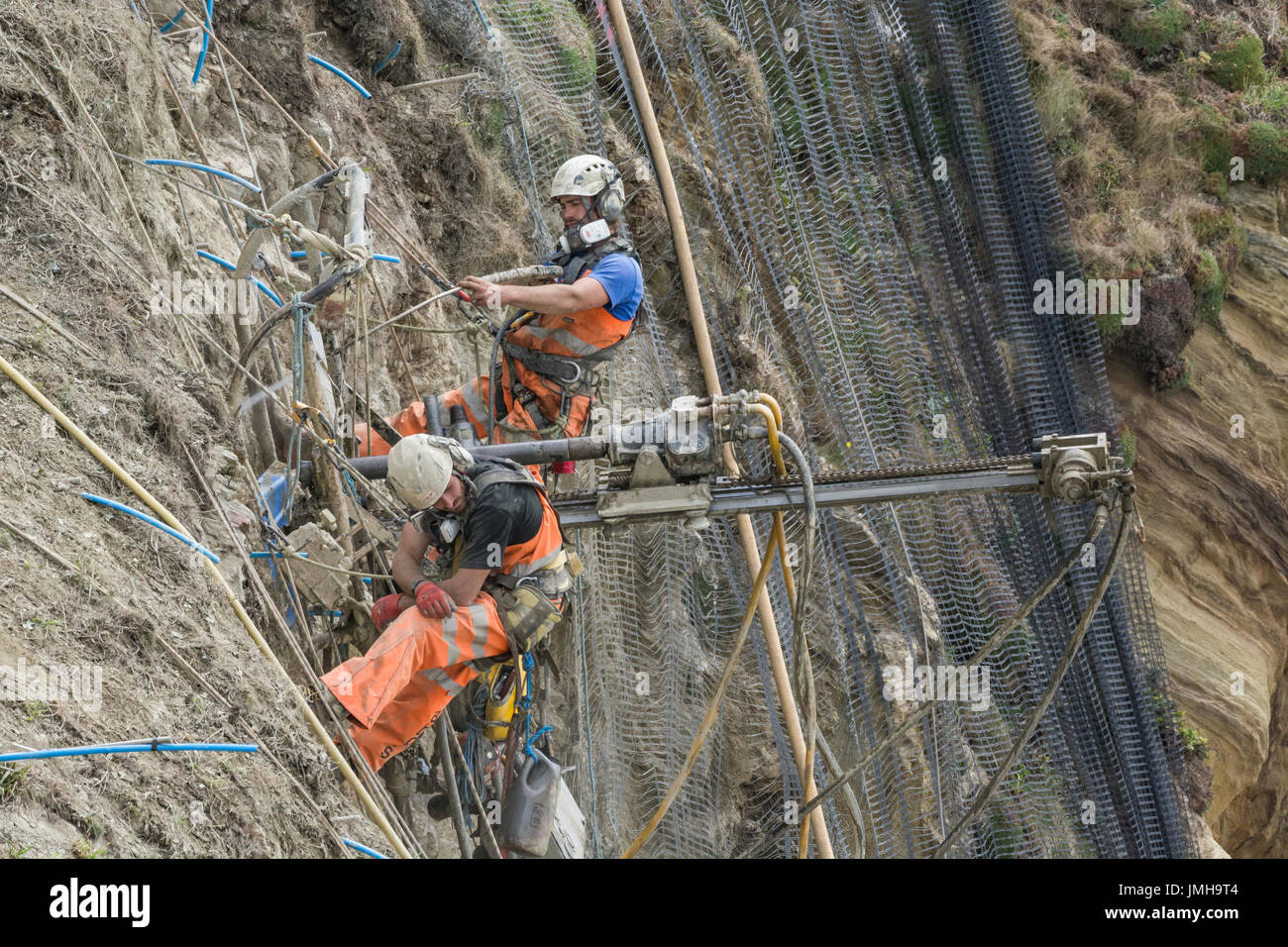 Telephoto shot two workmen drilling holes for cliff stabilisation rock bolts and subsequent rockfall mesh attachment. Concept International Rock Day. - Stock Image
