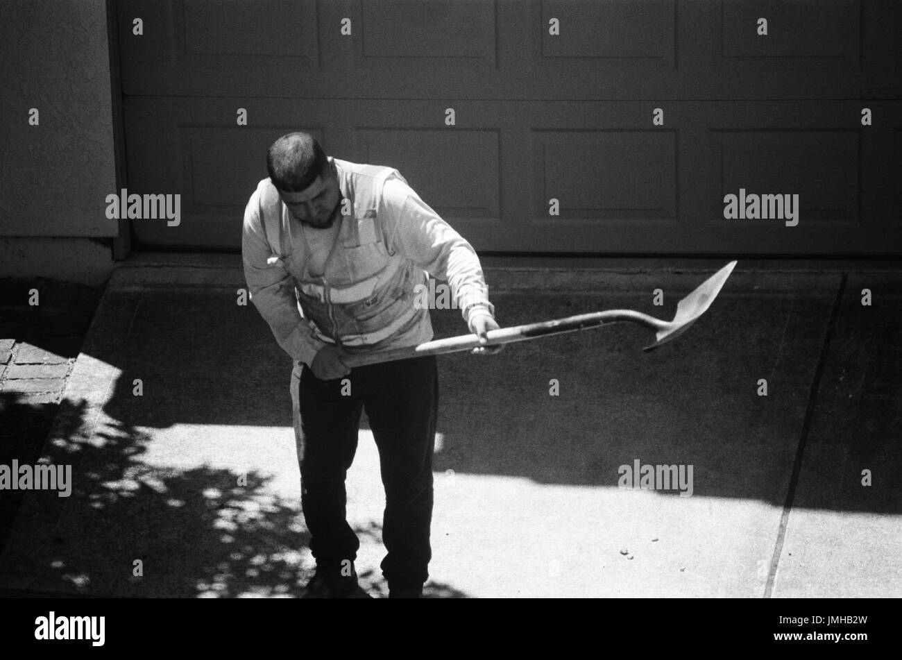 A construction worker bends in the hot sun as he prepares to lift a load of asphalt with a long shovel, San Ramon, California, June 26, 2017. - Stock Image