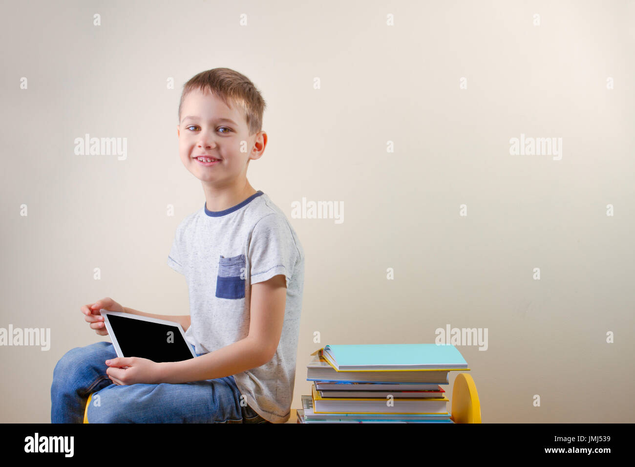 Smiling boy with tablet computer and stack of books near him - Stock Image