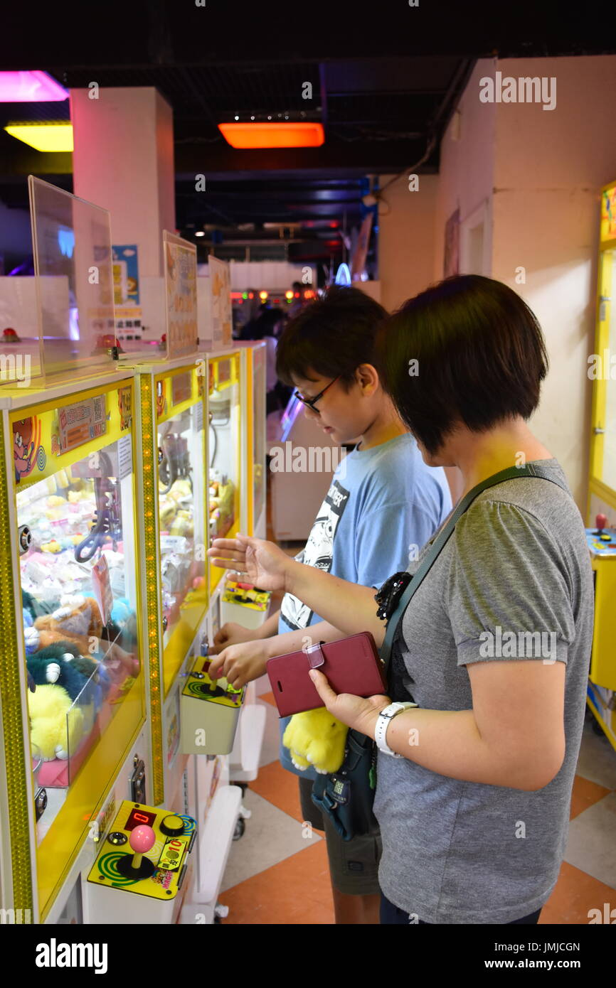 These games are very popular in Taiwan, just drop a 10NT coin in and try to get the claw to pick up your favorite toy, then drop it in the hole. - Stock Image