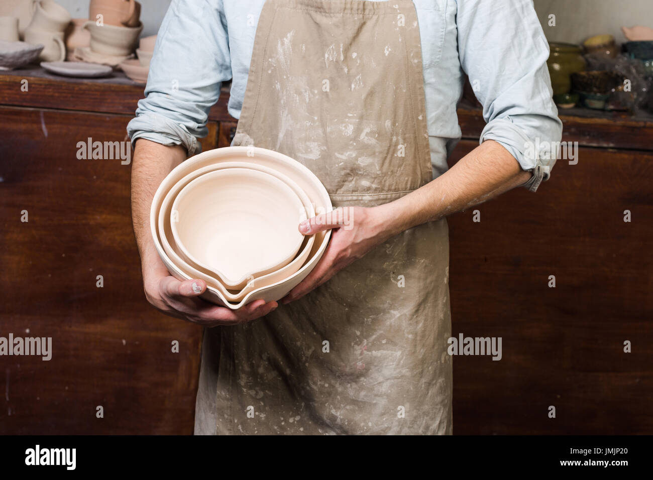 pottery, tools, ceramics art concept - closeup on male ceramist hands at workplace with baked bowls, cute finished clay utensils, wooden surface backg - Stock Image