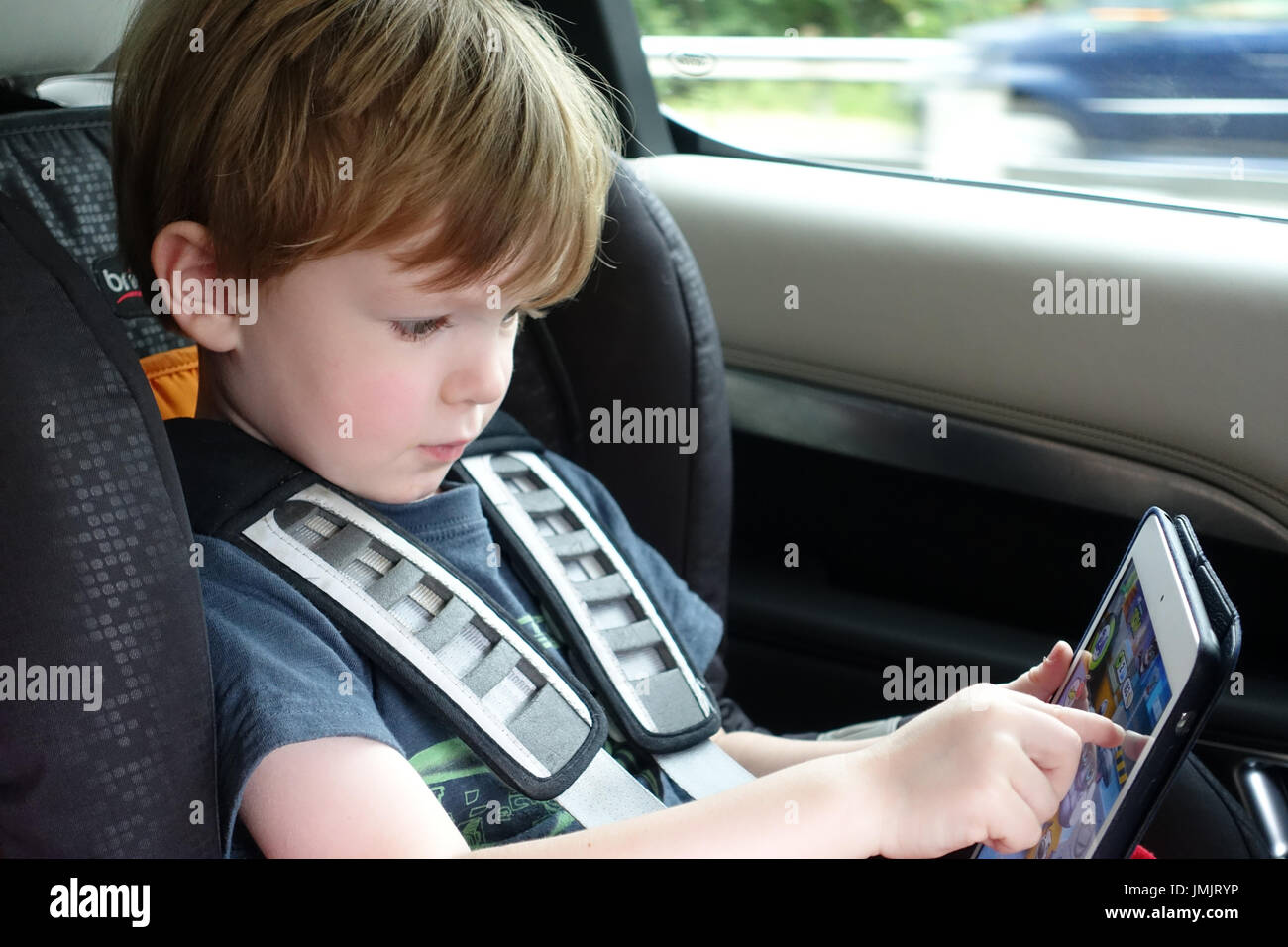 Child playing on an iPad during a car journey - Stock Image