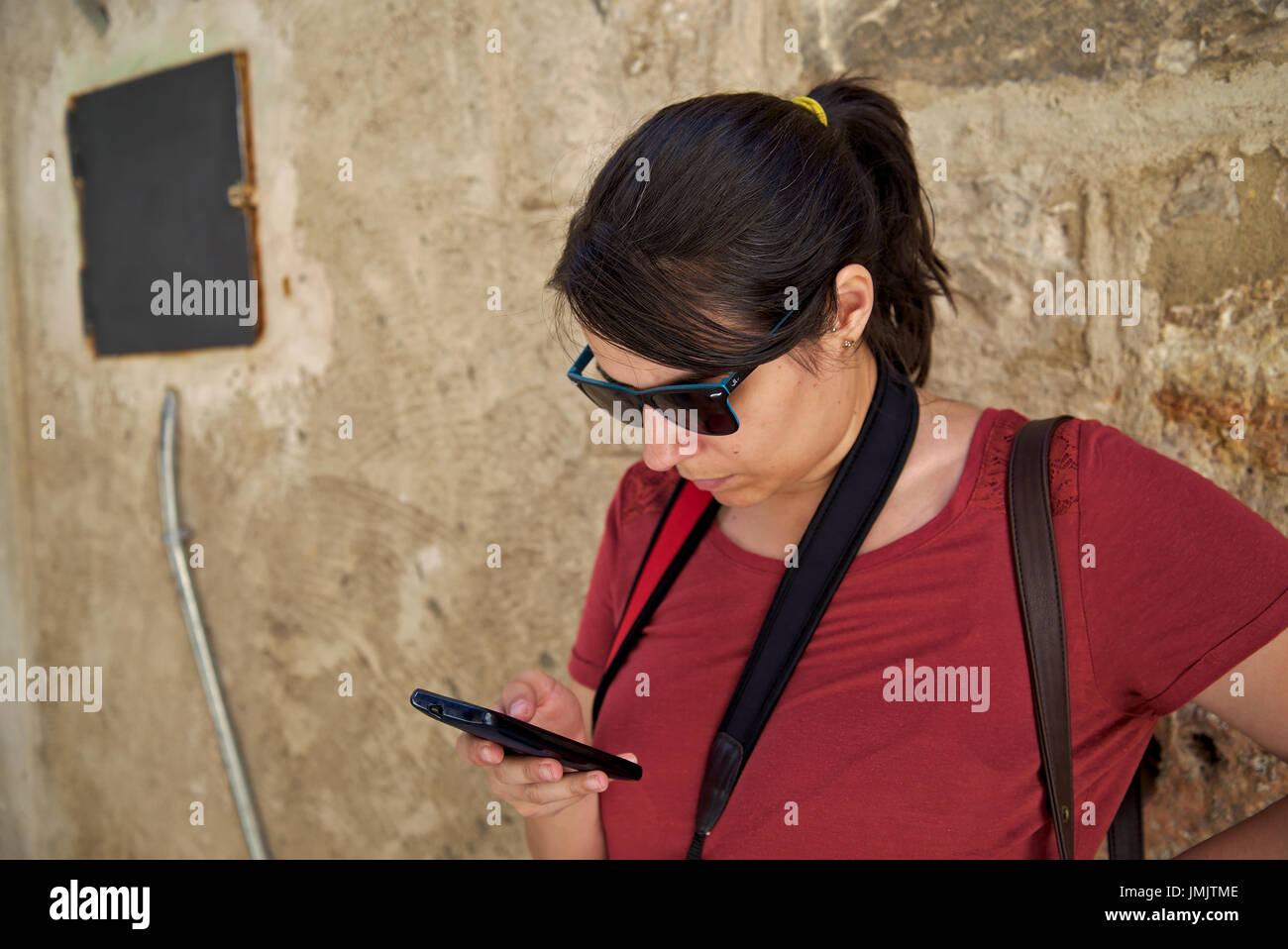 Woman with sunglasses and pigtail dressed on a red T-Shirt with a camera strap on her neck checks her smartphone on a centric street of Cuenca, Spain. - Stock Image