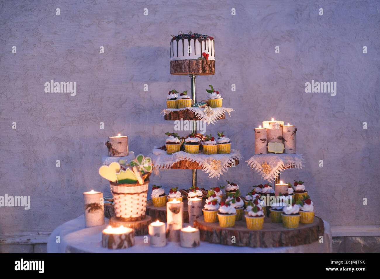 Wedding cake and cupcakes with candles on a shelf made of wood - Stock Image