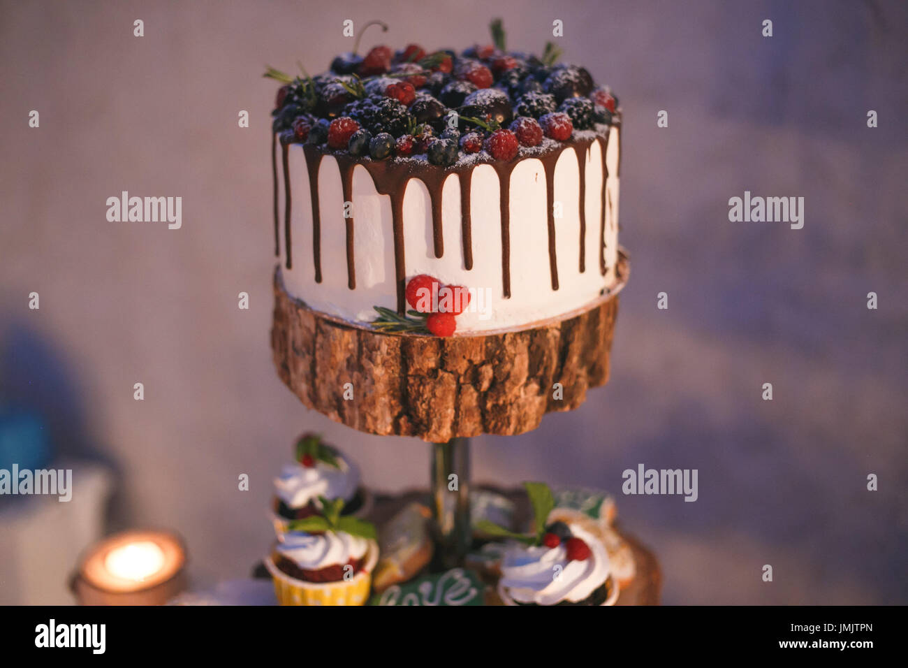 Cake and cupcakes with berries on a wooden shelf in candle light. - Stock Image