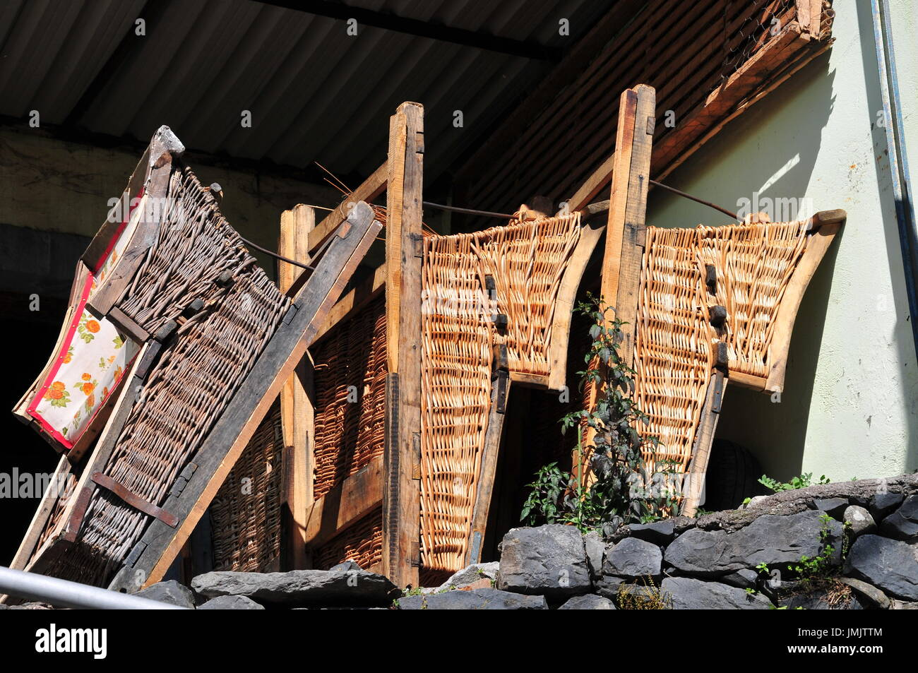 Wooden/wicker toboggans used in the tourist industry in Madeira to take people down the hill on the roadways, steered by two operators - Stock Image