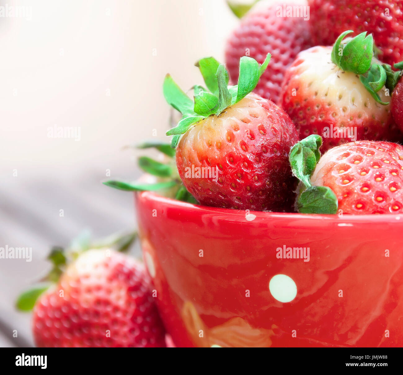 Colored photo of some strawberries inside a red cup Stock Photo