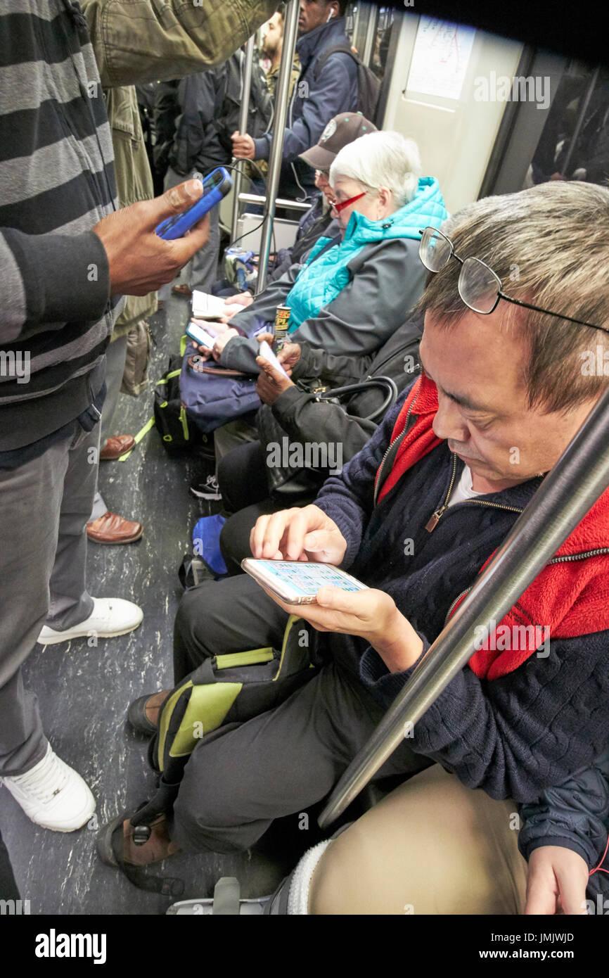 passengers using smartphones inside train on Boston MBTA underground USA - Stock Image