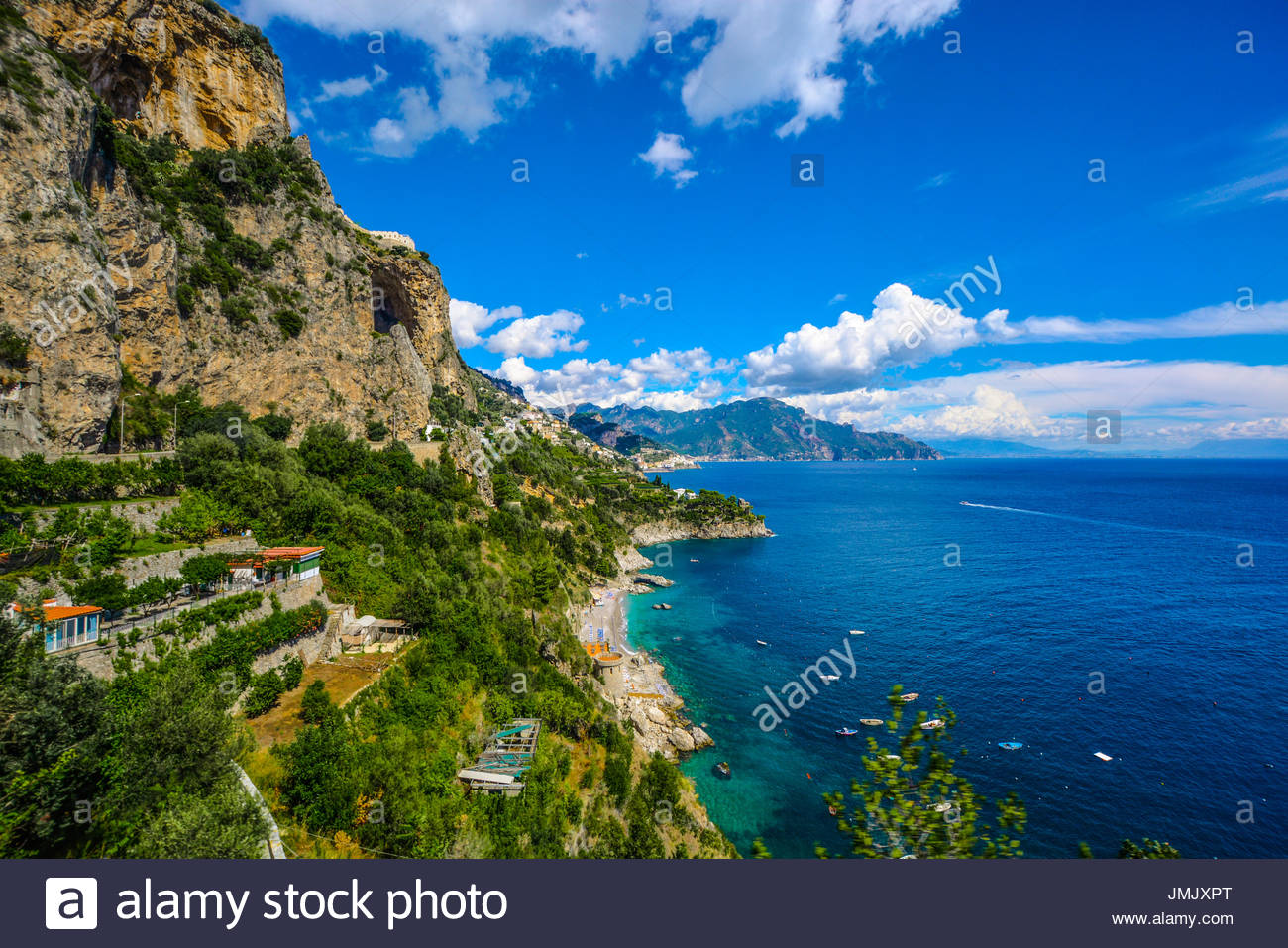 The Amalfi Coast near Positano and Sorrento on a warm summer afternoon with boats in the water and homes and resorts on the hillside - Stock Image