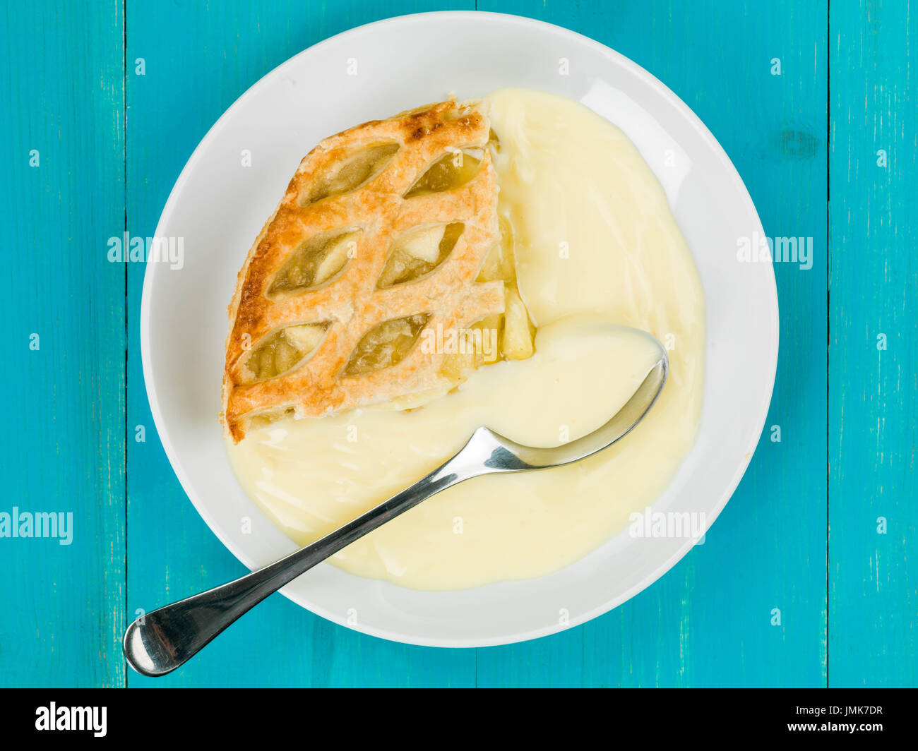 Apple Pie And Custard Dessert Against a Blue Wooden Background - Stock Image