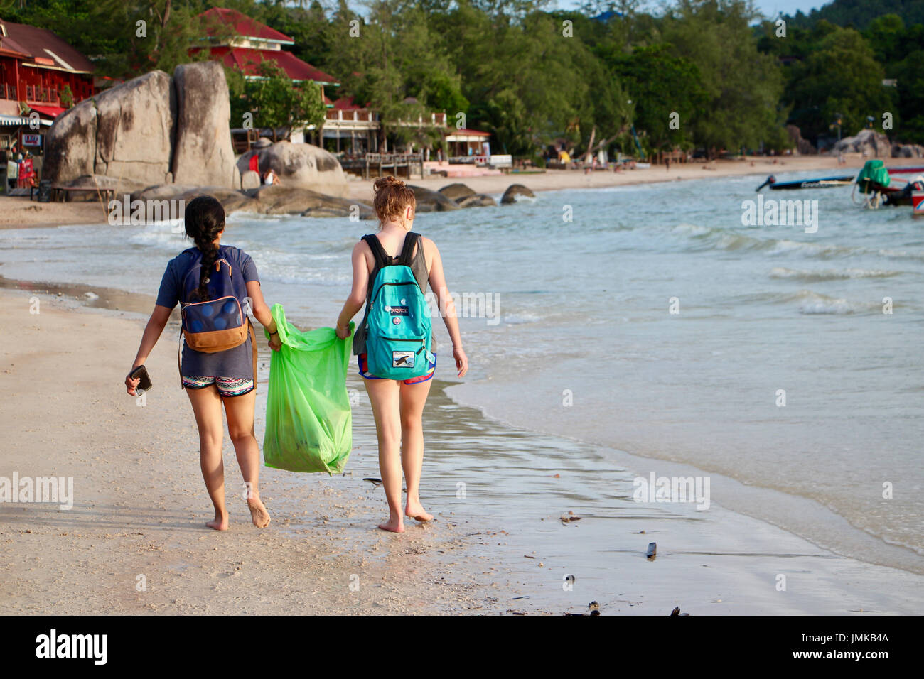 Two girls help clean up the beach on Koh Tao - Stock Image