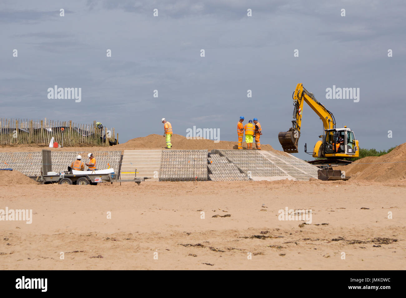 Men working on a beach building access points and reinforcing banks - Stock Image