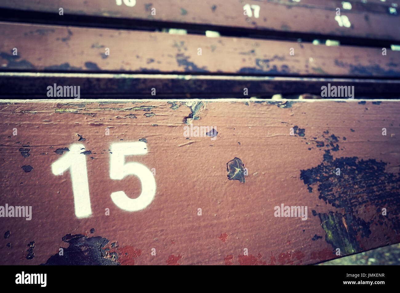 Number fifteen painted on an old wooden seat, conceptual picture with copy space on the right. - Stock Image