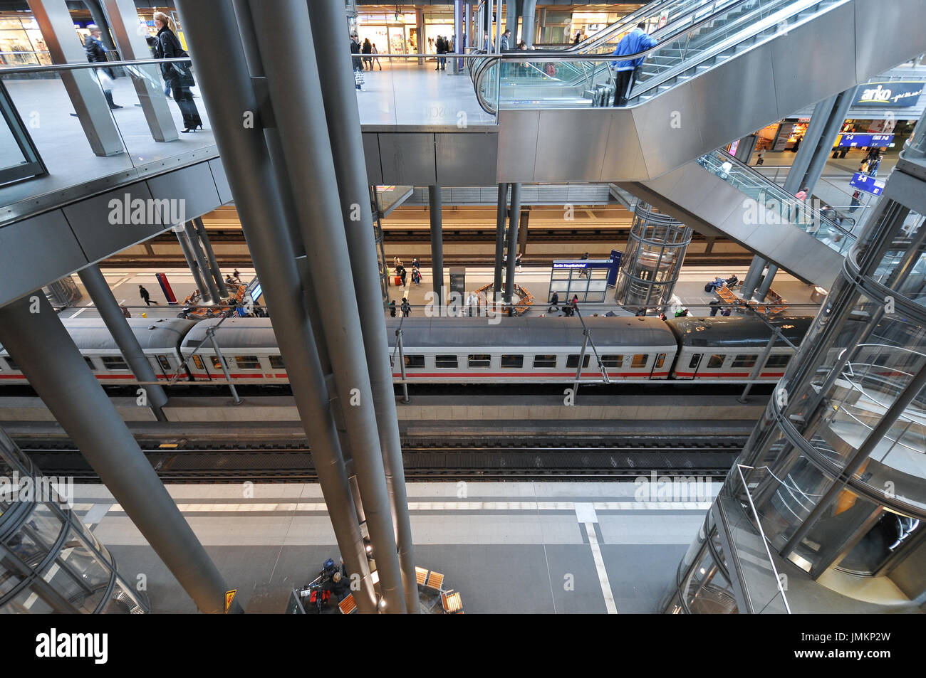 View inside Berlin Hauptbahnhof, central station with trains and people present - Stock Image