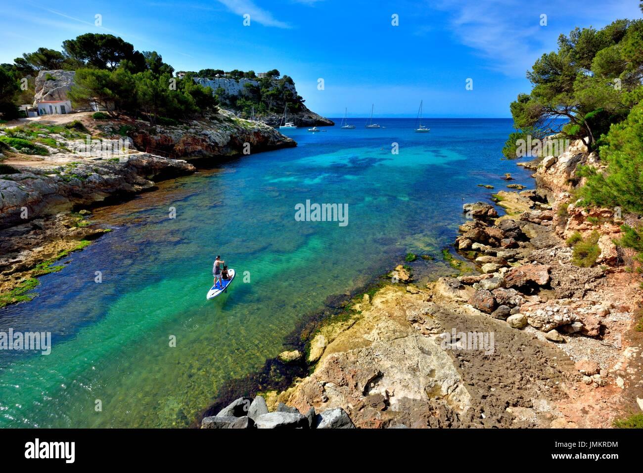Young couple paddle boarding Cala Galdana Menorca Minorca - Stock Image
