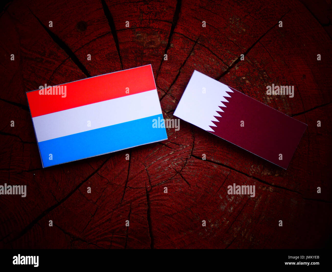 Luxembourg flag with Qatari flag on a tree stump isolated Stock Photo