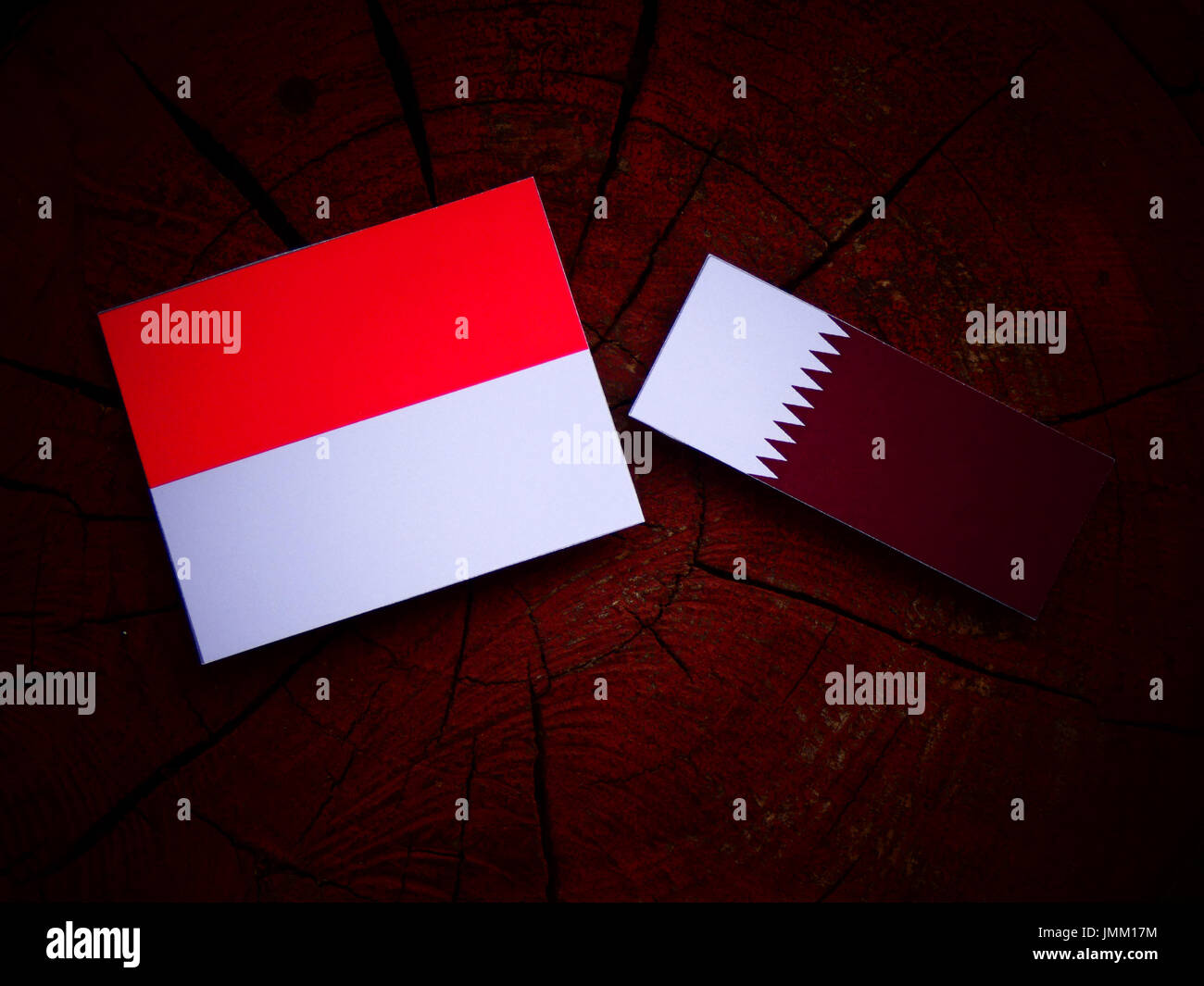 Monaco flag with Qatari flag on a tree stump isolated Stock Photo