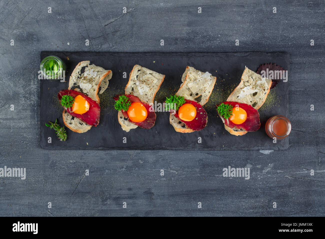 Four tiny appetizers with cured met, yolk and parmegano cheese on stone board with copyspace. Top view - Stock Image