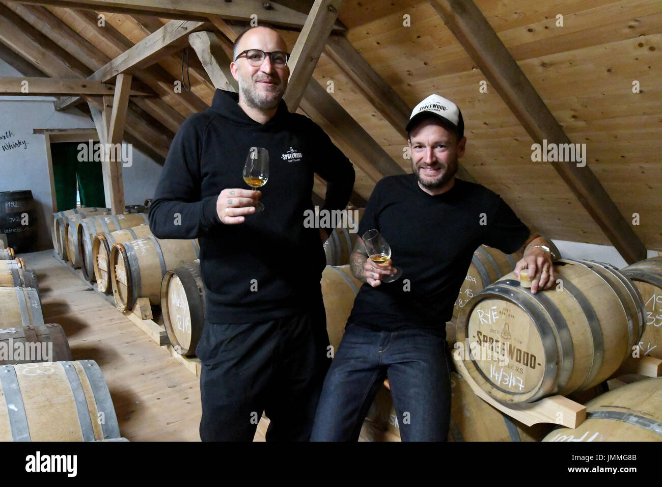 Schlepzig, Germany. 26th July, 2017. Owners Steffen Lohr (l) and Bastian Heuser test a whiskey in their storage Stock Photo