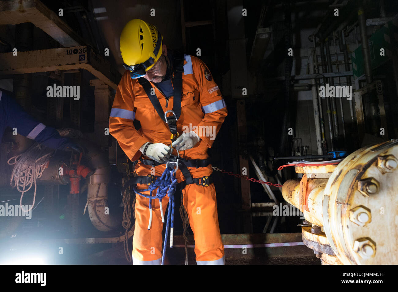 An industrial rope access technician setting up harness, on north sea oil and gas installation wearing Orange coveralls. credit: LEE RAMSDEN / ALAMY - Stock Image