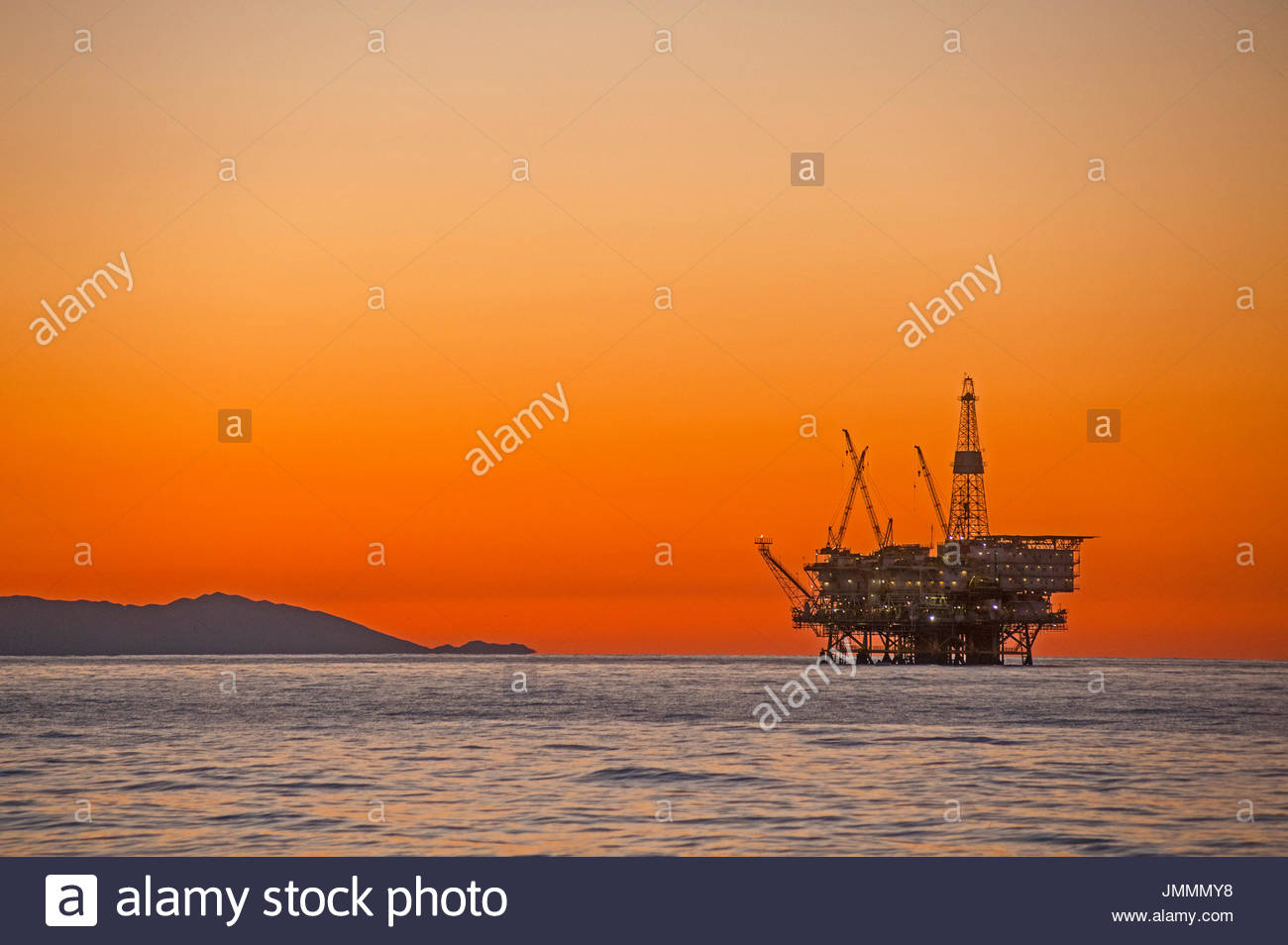 Oil drilling and pumping platforms rise out of the Pacific near Santa Catalina Island. - Stock Image