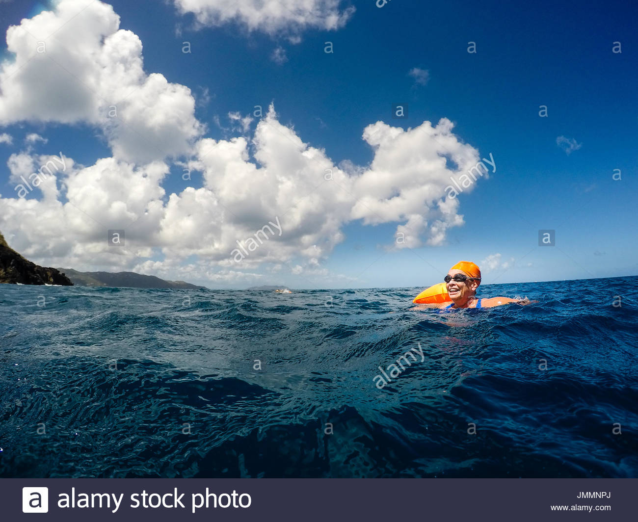 A woman in a blue bathing suit, goggles and orange swim cap smailes as she treads waterr. - Stock Image