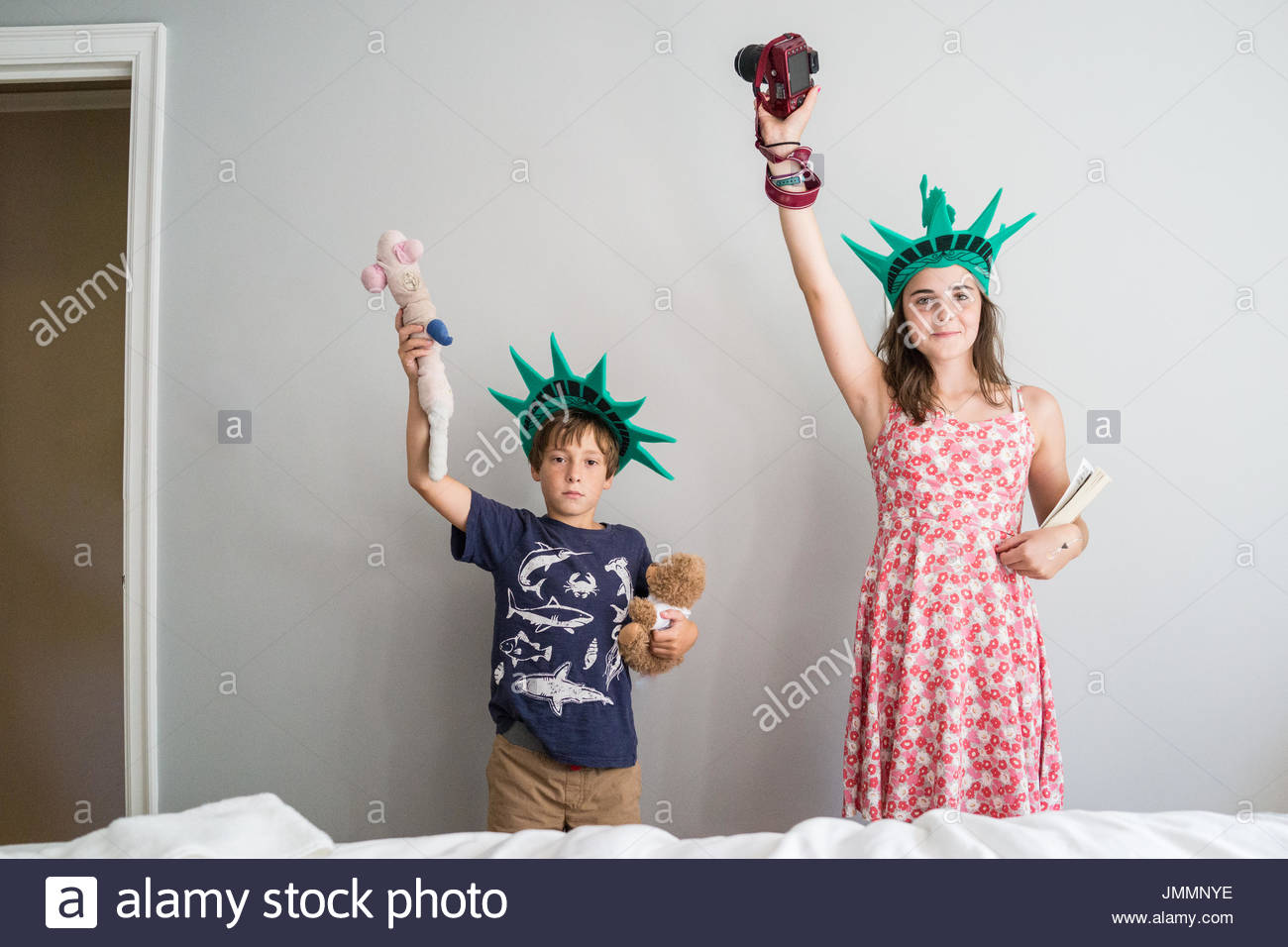 A young boy and a teenage girl pose like the statue of liberty against a gray wall. - Stock Image