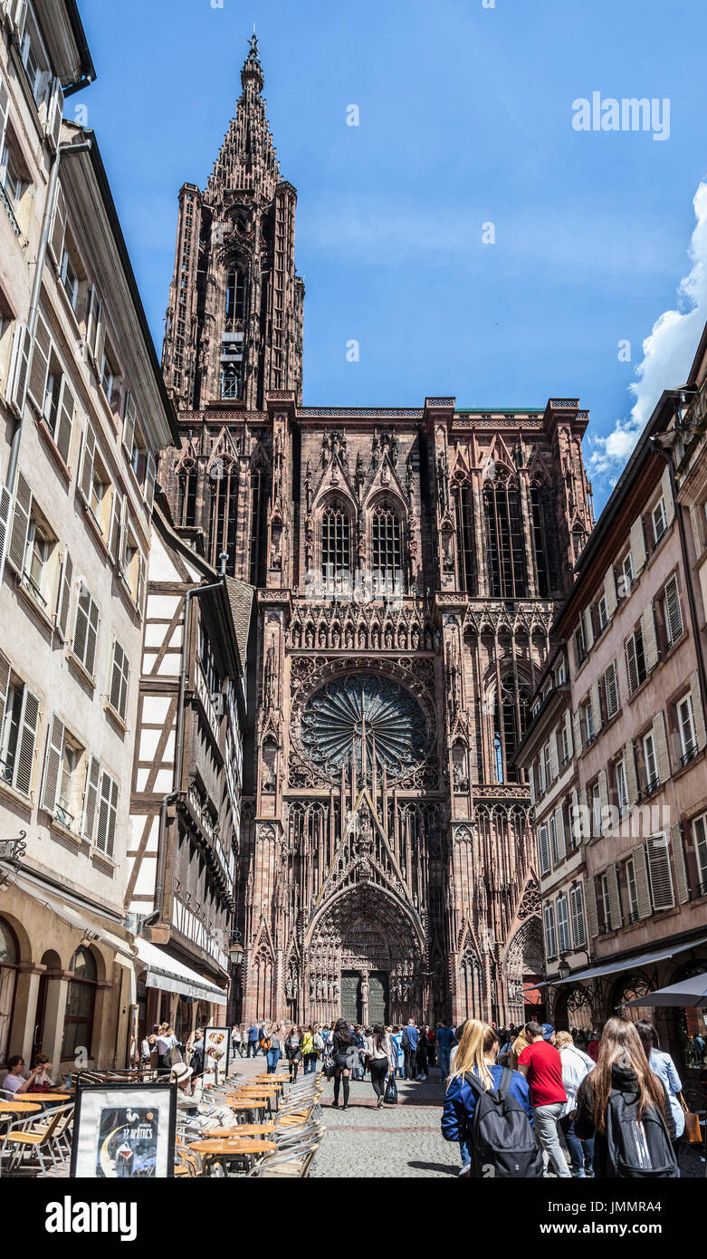People, mainly tourists, in Rue Mercière, walking towards the west facade of Cathédrale Notre-Dame de Strasbourg - Stock Image