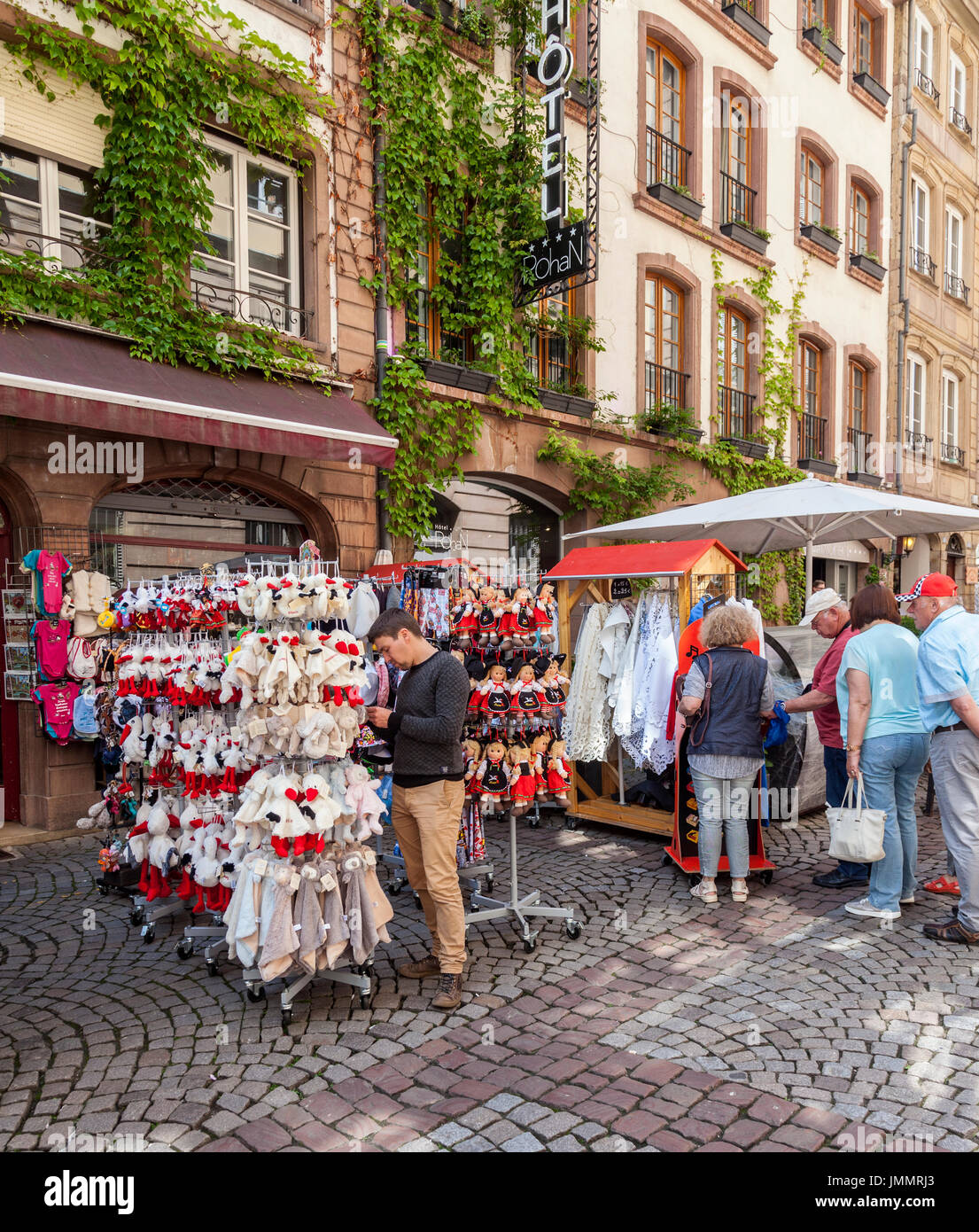 Tourists in Rue du Maroquin, Strasbourg, browsing typical gifts from Alsace outside Le Petit Alsacien gift shop. Hotel Rohan entrance in background. - Stock Image