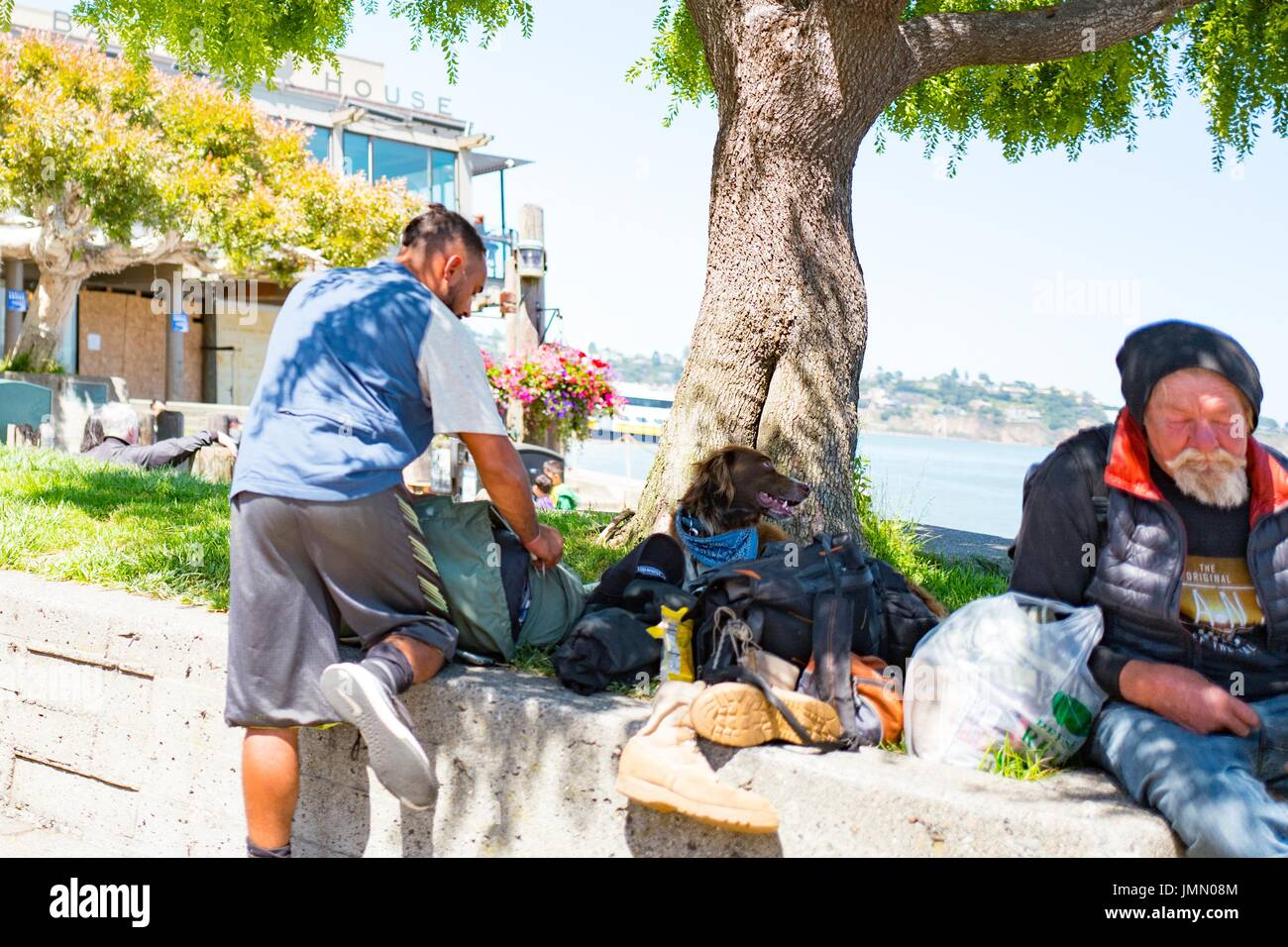A homeless man and a traveler with a dog sit in Yee Tock Chee park on Bridgeway Road in the San Francisco Bay Area town of Sausalito, California, June 29, 2017. - Stock Image