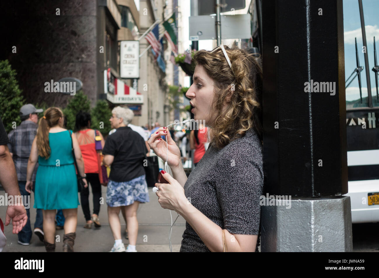 Young woman, with a curly hair, talking on the phone using headphone / earbuds, holding microphone piece in her hand, while standing on the street - Stock Image