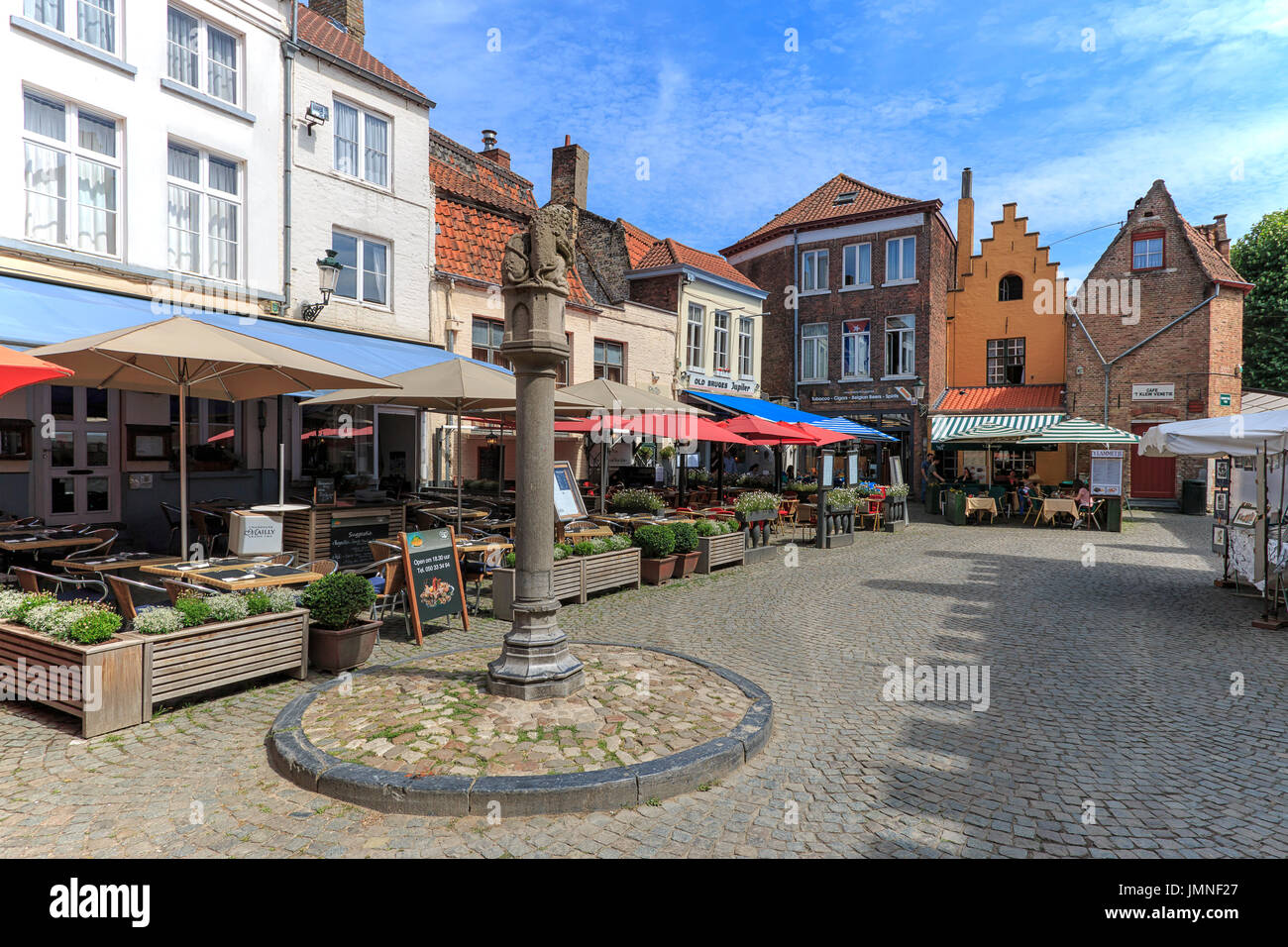 Bruges, Belgium - July 7, 2017: Tourists eating mussels and french fries in the restaurants not far from the Market Square of Bruges - Stock Image