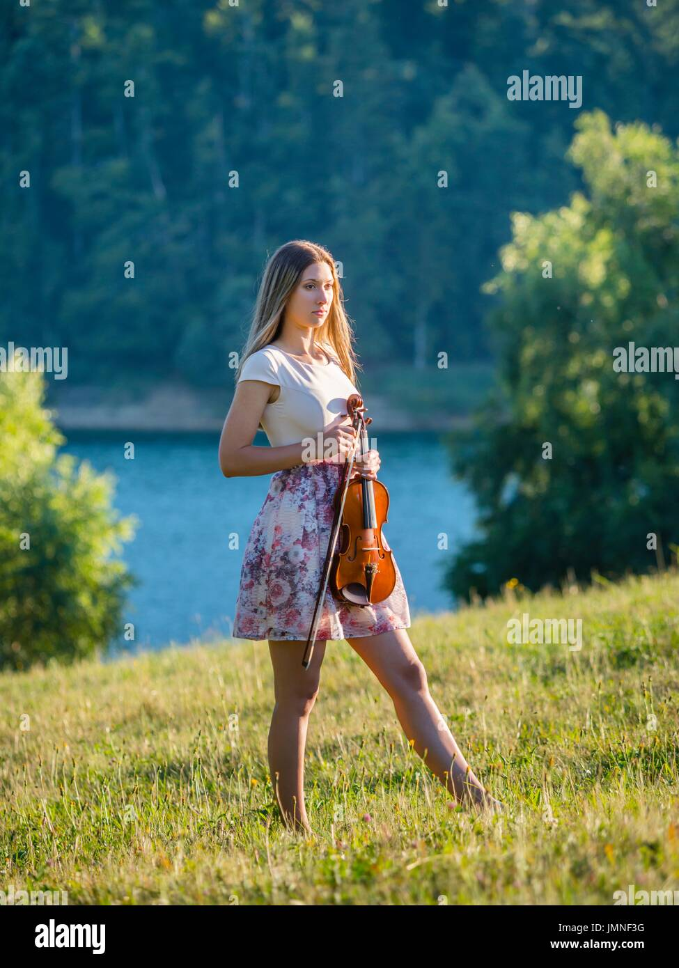 Young female violinist in nature near lake nostalgia nostalgic in short clothing with model-released release MR Stock Photo