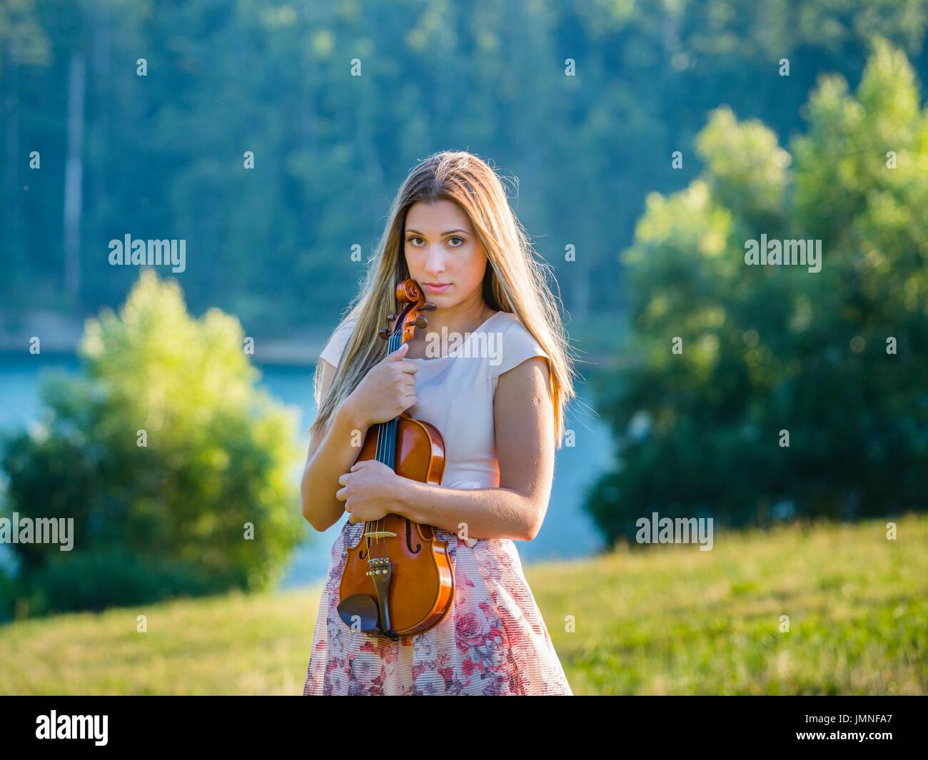 Young female violinist in nature near edge lake alone lonesome solitude loneliness innocent look innocence silence Stock Photo