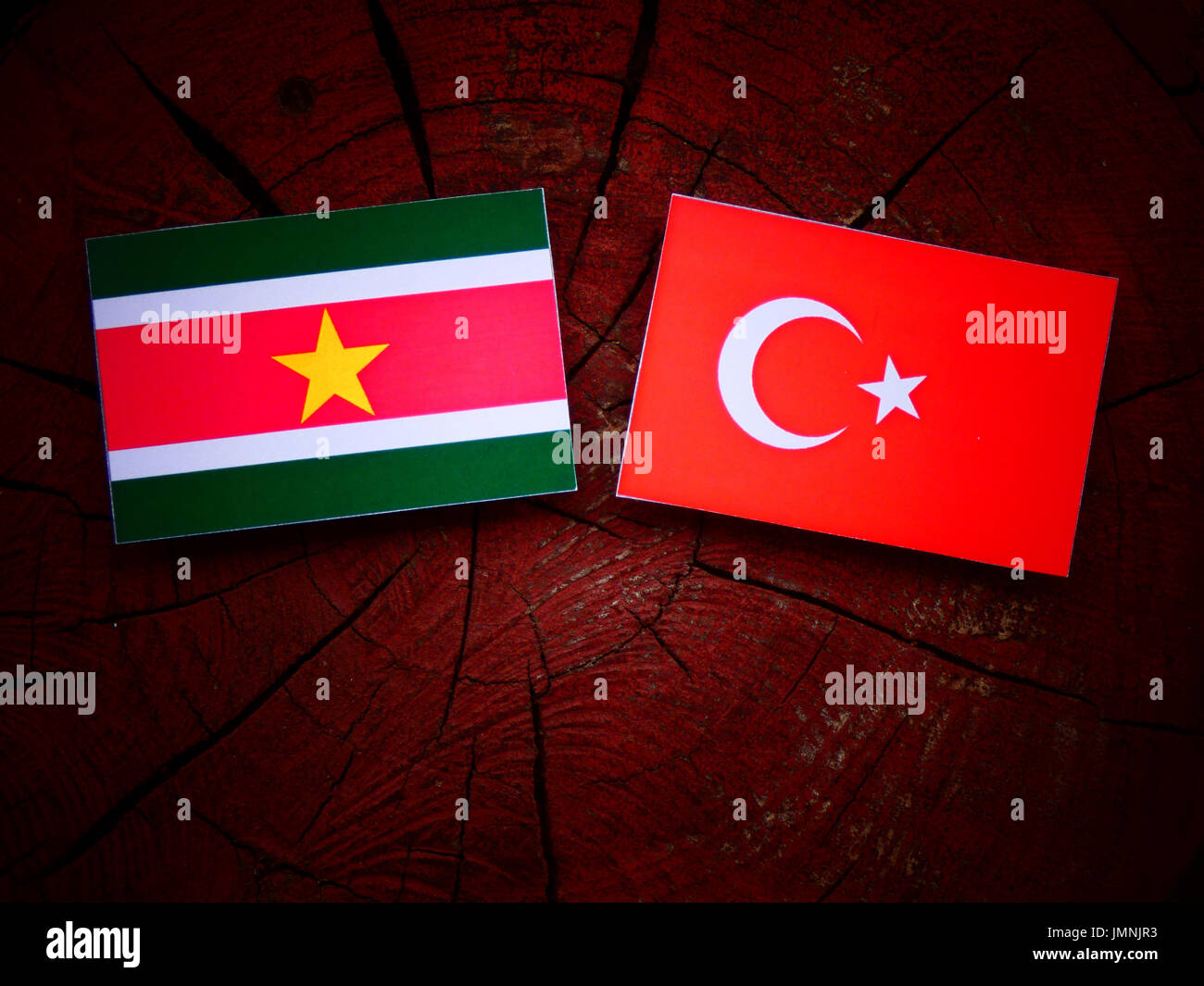 Suriname flag with Turkish flag on a tree stump isolated - Stock Image