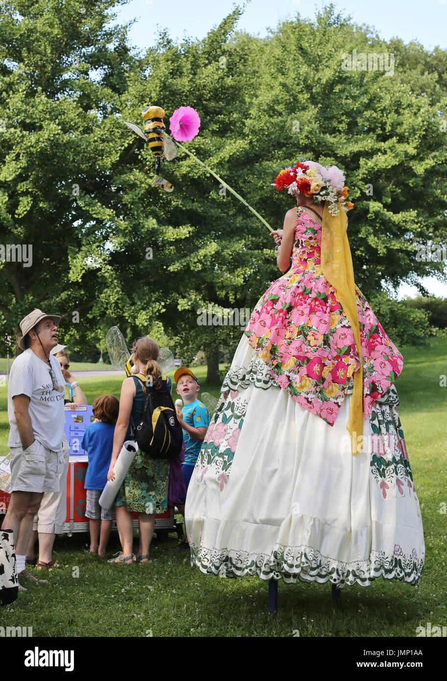 A woman on stilts, at the pollinator party in Minneapolis, Minnesota, USA. - Stock Image