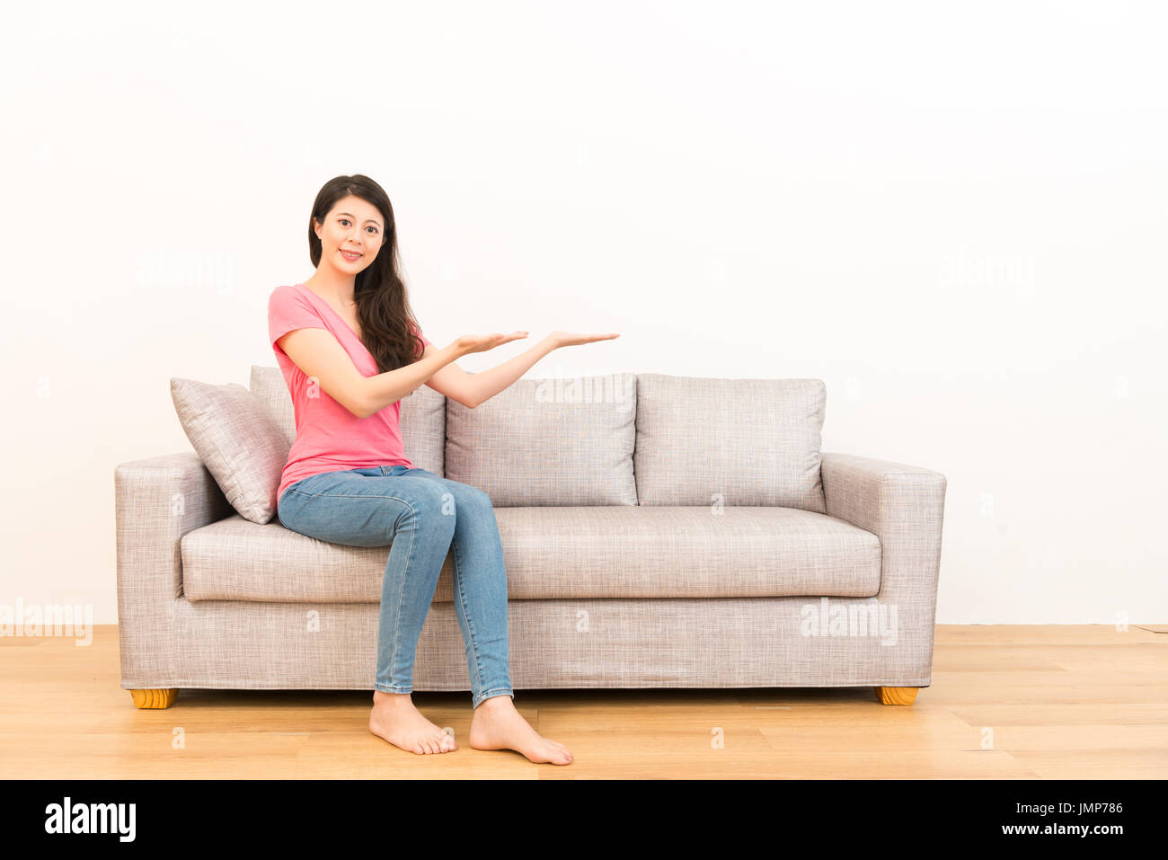 Tremendous Smiling Asian Woman Sitting On The Couch Sofa Showing Gmtry Best Dining Table And Chair Ideas Images Gmtryco