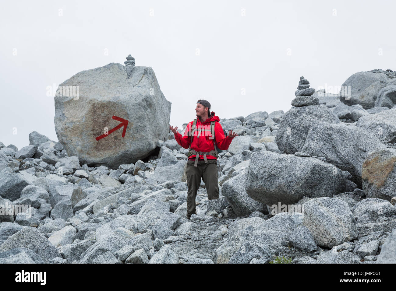 The trail is marked with two large cairns and a giant red arrow painted on a boulder, but this man appears to be lost. Grey, cloudy sky overhead - Stock Image