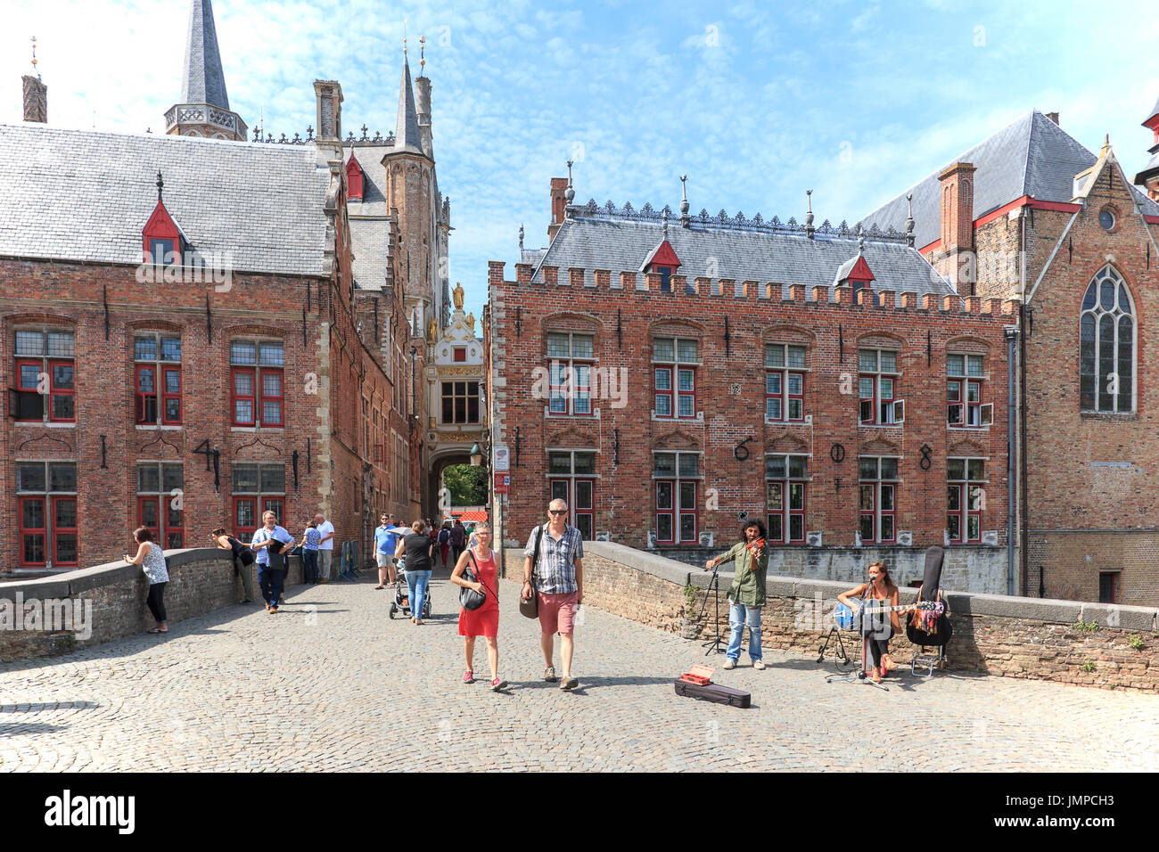 Bruges, Belgium - July 7, 2017: Tourists walking in the narrow streets in the center of Bruges. Bruges is also called the Venice of the North due to t - Stock Image
