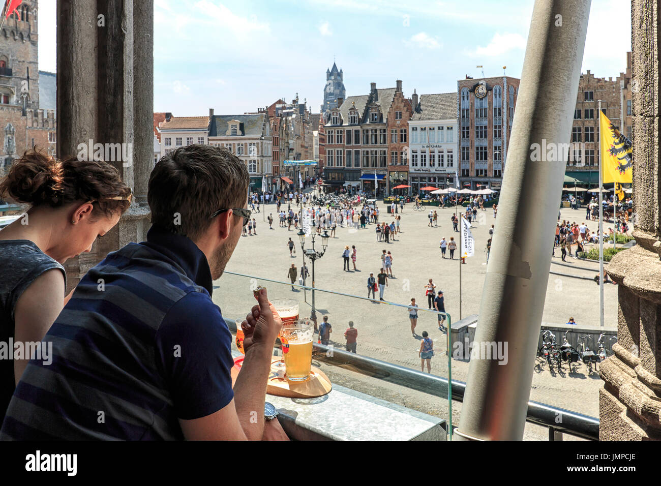 Bruges, Belgium - July 7, 2017: Tourists drinking beer and eating chocolate while enjoying the a panoramic view of the market square in the center of  - Stock Image