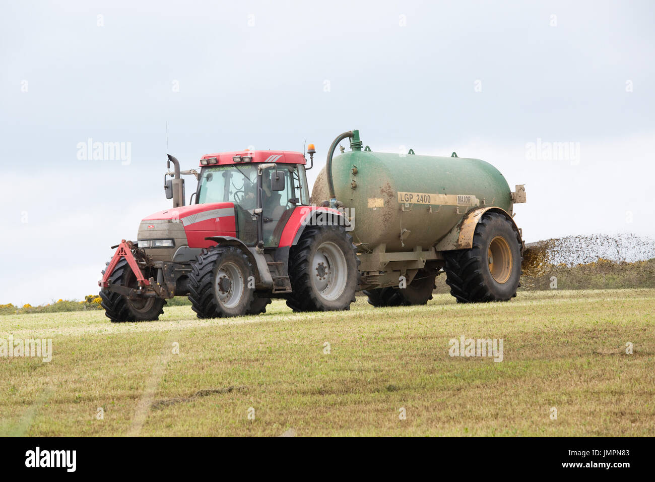 Tractor working with muck spreader Pembrokeshire UK - Stock Image