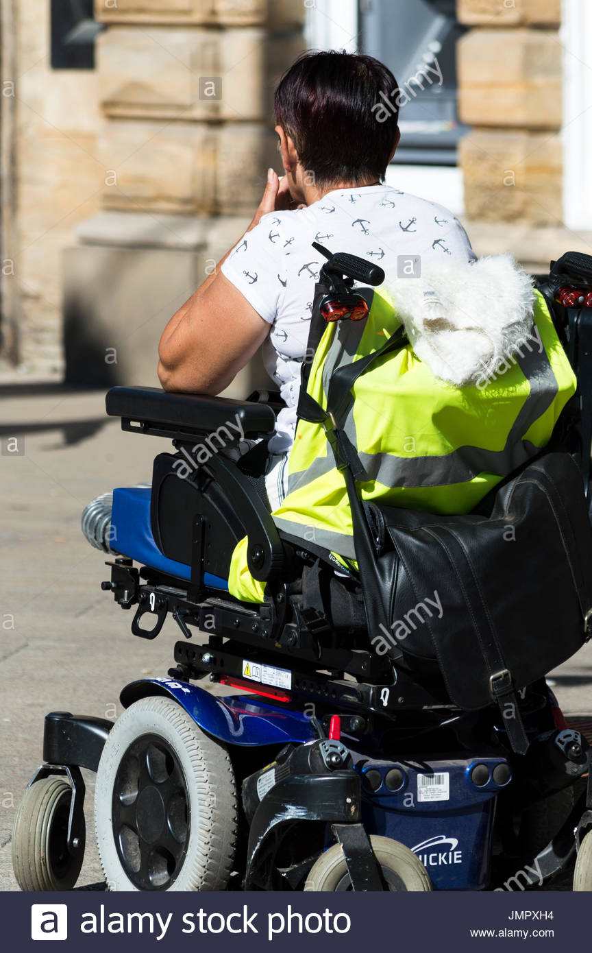 Close-up from behind of a woman sat, waiting, in a wheelchair, Yeovil, Somerset, England Stock Photo